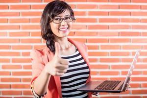 estudante asiática com laptop mostrando o polegar foto