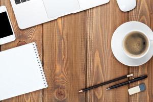 uma mesa de escritório com um computador, suprimentos e uma xícara de café