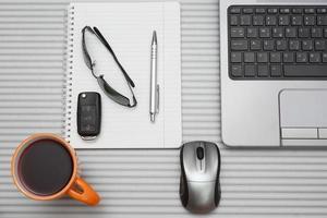 local de trabalho, laptop e bloco de notas na mesa moderna foto