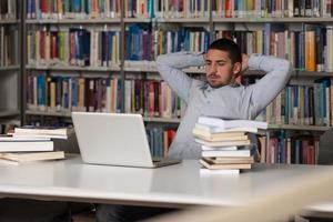 um estudante masculino em uma biblioteca, olhando para o laptop foto