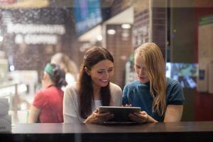 duas mulheres conversam alegremente no restaurante usando tablet eletrônico