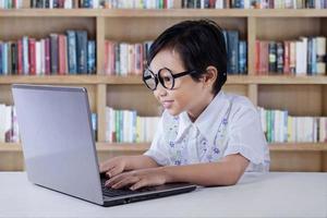 linda garotinha digitando no laptop na biblioteca foto