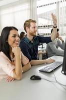 mulher jovem e bonita e um homem levantando as mãos em sala de aula foto