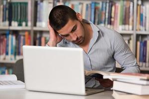 estudante universitário masculino estressado sobre sua lição de casa foto