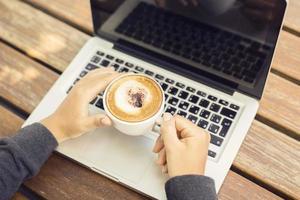 laptop e cappuccino em uma mesa de madeira