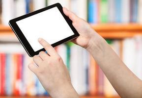 dedo toca tablet pc na frente das prateleiras de livros foto