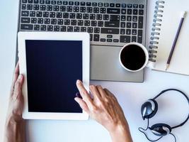 mãos segurando o tablet touch gadget de computador com laptop e café foto