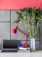 mesa de escritório moderna com laptop, lâmpada e vaso de flores