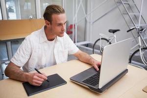 homem usando a mesa digitalizadora para fazer o trabalho foto