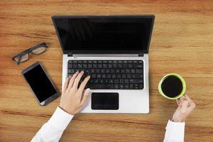 mãos segurando café e usando o laptop foto