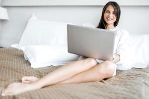 mulher bonita camisa usando um notebook na cama foto