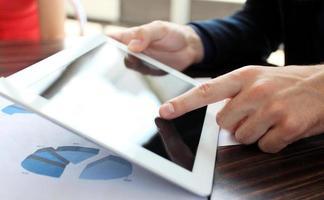 mão tocando no pc tablet digital moderno no local de trabalho foto