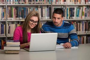 estudantes felizes trabalhando com o laptop na biblioteca foto