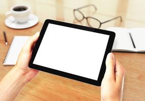 mãos segurando um tablet, óculos e cadernos no fundo