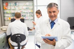 farmacêutico sênior usando o tablet pc foto