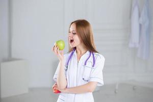 médico mordendo uma maçã verde.