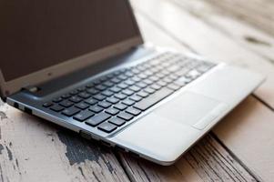 close-up teclado prata computador portátil aberto no chão de madeira foto