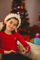 menina festiva usando o tablet pc no sofá foto