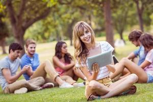 loira bonita usando tablet no parque foto