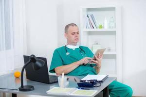 médico trabalhando com um computador tablet em seu escritório
