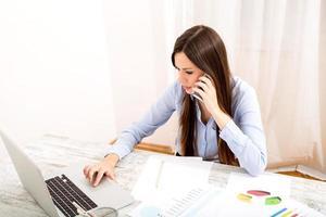 trabalhando no escritório e falando pelo telefone foto