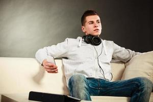 cara com tablet fones de ouvido telefone no sofá