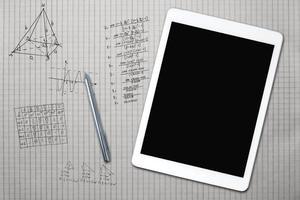 tablet e esboços matemáticos em uma folha de quadrado foto