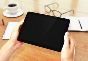 mãos segurando o tablet digital no local de trabalho foto