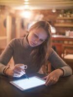 mulher com tablet pc e caneta no café foto