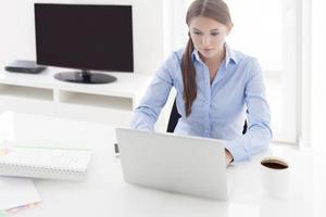 empresária trabalhando em seu laptop na frente da televisão foto