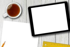 tablet digital, xícara de chá e folha de papel na mesa de madeira