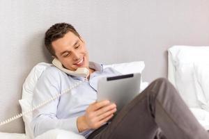 empresário com tablet pc e telefone no quarto de hotel