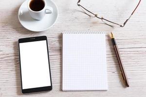 caderno com caneta, telefone inteligente e xícara de café foto