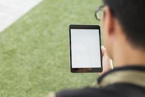 homem olha um tablet em branco foto