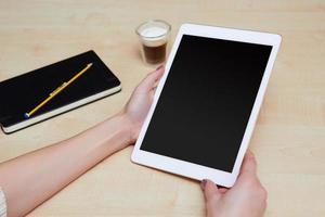 pessoa segurando uma pastilha branca digital com tela em branco foto