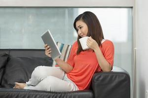 mulher asiática em casa lendo um tablet pc. foto