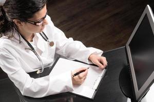 médica na frente do computador, escrevendo sobre uma prancheta foto