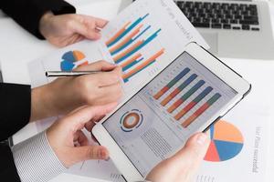 close-up da equipe de negócios usando tablet digital com d financeiro foto