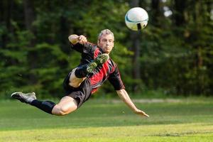 jogador de futebol em um chute de bicicleta foto