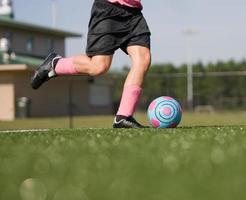 bola de chute de jogador de futebol de menina foto