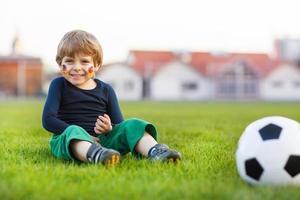 menino loiro de 4 jogando futebol com campo de futebol onl