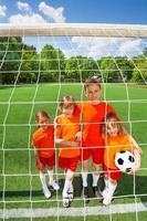 crianças sorridentes em pé perto de futebol