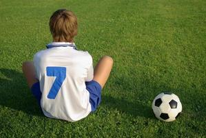 menino com uma bola de futebol foto