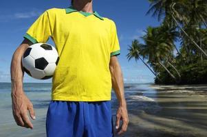 jogador de futebol da equipe brasil em pé na praia nordeste foto