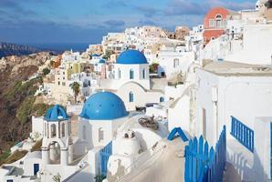 santorini - procure cúpulas da igreja tipicamente azuis em oia. foto