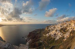 cidade branca na encosta da colina, pôr do sol, oia, santorini, grécia foto