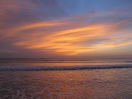 pôr do sol colorido brilhante no mar com belas nuvens