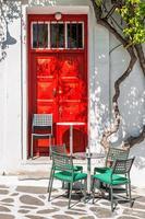 rua café terraço na frente de uma porta vermelha, mykonos foto