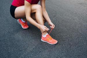 corredor feminino amarrando os sapatos na trilha foto