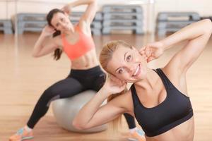 par de mulheres dong alongamento na bola de fitness foto